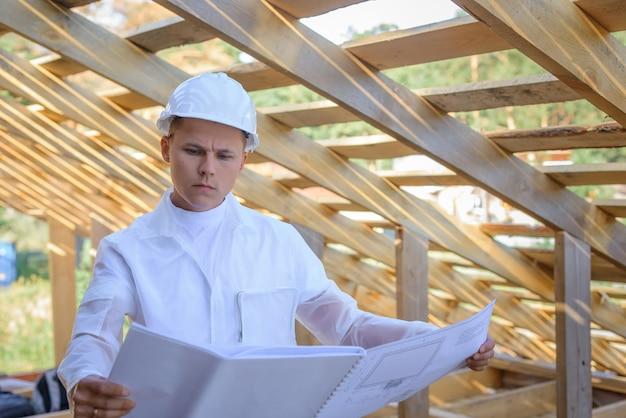 Ingeniero de sexo masculino joven que mira trabajos de construcción. arquitecto con plano de marco de madera. usar casco por seguridad.