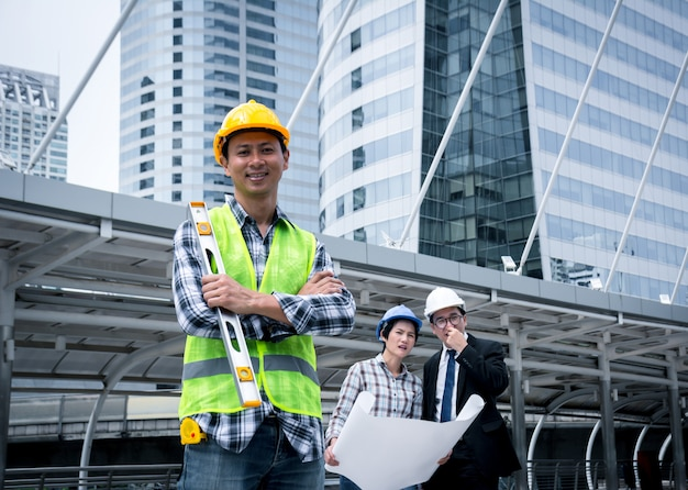 Ingeniero de sexo masculino de pie con los brazos cruzados y sosteniendo el medidor de nivel de agua