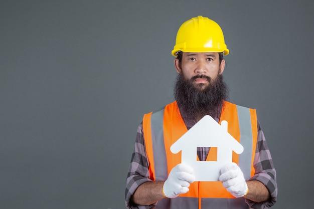 Un ingeniero de sexo masculino que lleva un casco de seguridad amarillo que lleva a cabo un símbolo de la casa blanca en un gris.
