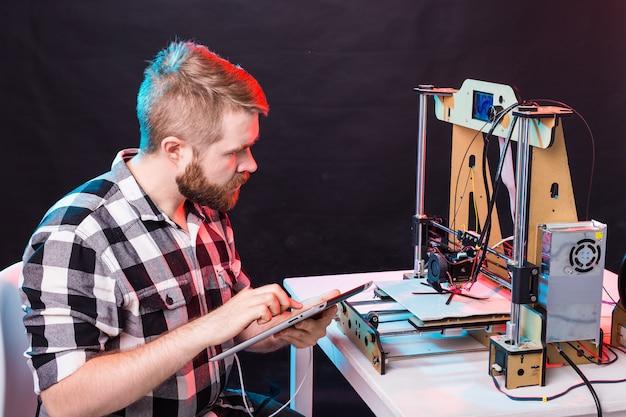 Ingeniero de sexo masculino que trabaja de noche en el laboratorio, está ajustando los componentes de una impresora.