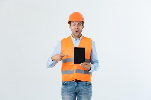 Ingeniero de sexo masculino sorprendido que muestra la pantalla de la tableta, mira con la boca abierta como recuerda acerca de la reunión importante. hombre en situación estresante. concepto sorpresa y conmoción.