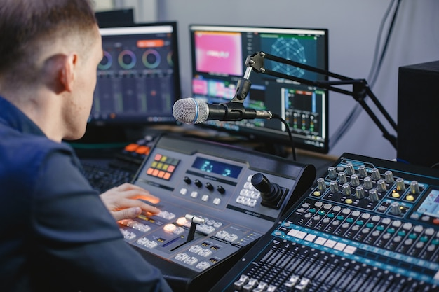 Ingeniero de sonido trabajando en estudio con equipo.