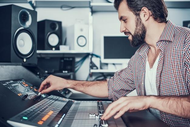 Ingeniero de sonido utilizando mesa de mezcla de estudio.