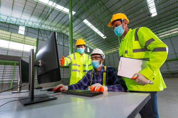 Ingeniero supervisor asiático consultar con los trabajadores del almacén