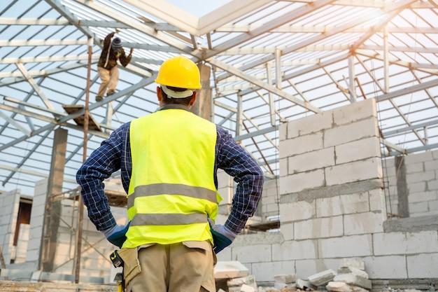 Ingeniero técnico buscando y analizando un proyecto de construcción inacabado.