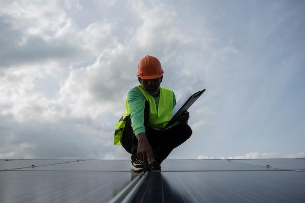 El ingeniero técnico verifica el mantenimiento de los paneles de células solares.