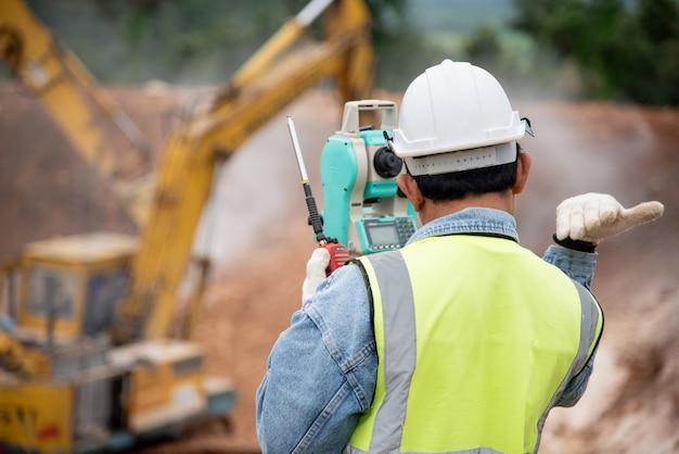 Ingeniero de topografía en sitio de construcción usa teodolito revisando trabajo de cimentación de excavación