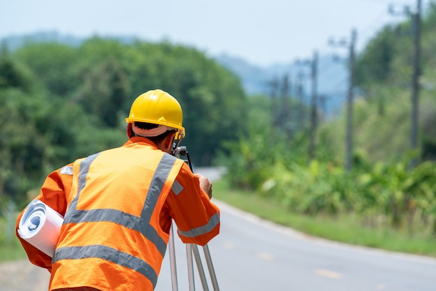 El ingeniero de topografía en el sitio de construcción utiliza la marca de teodolito en la carretera. concepto de construcción.