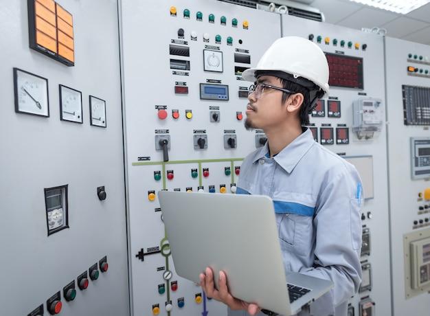 El ingeniero trabaja y verifica la distribución de energía eléctrica de la celda del estado en la sala de subestación de la planta de energía.