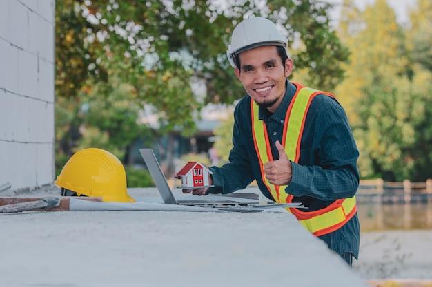 Ingeniero trabajador arquitecto feliz trabajando en la construcción del sitio de su computadora portátil