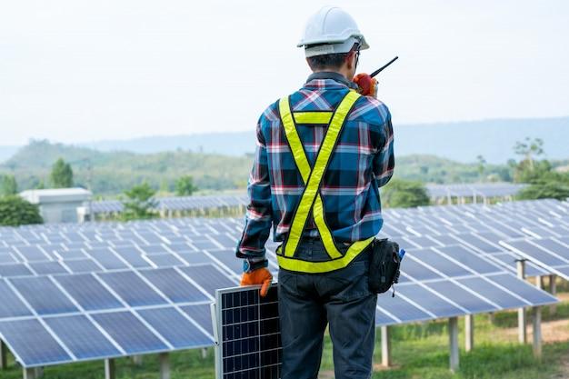 Ingeniero trabajando en el control y mantenimiento de equipos eléctricos en estaciones de plantas de energía solar, conceptos de energía renovable y energía solar.