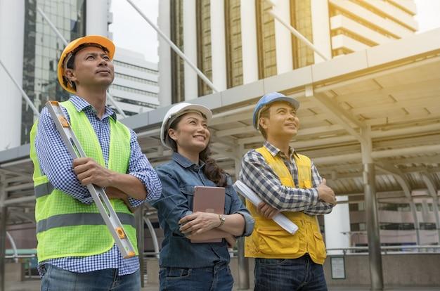 Ingeniero de trabajo en equipo asiático cruza el brazo y esperando el éxito