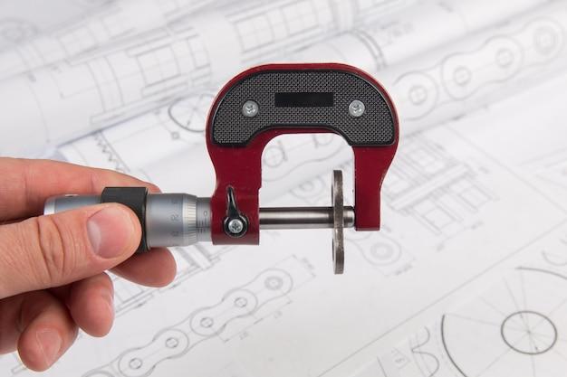 Ingeniero de trabajo. medición de la parte metálica con un calibrador en los planos de ingeniería.