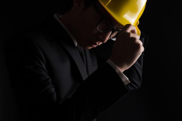 Ingeniero en traje negro sobre fondo negro aislado
