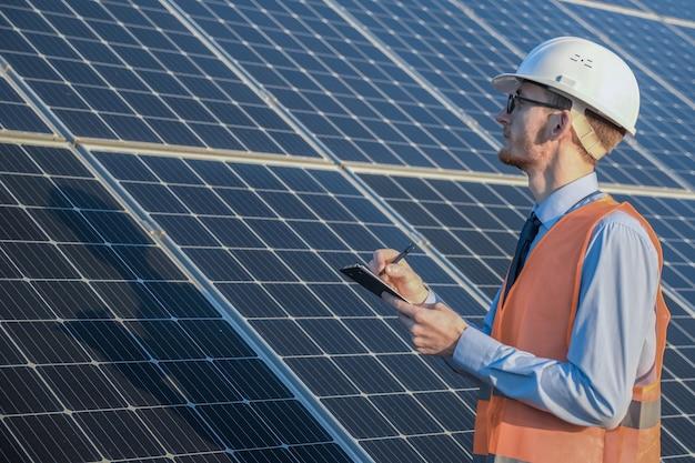 Ingeniero en uniforme de pie sobre un panel solar