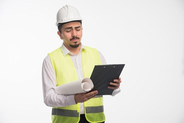 Ingeniero en uniforme revisando la lista de tareas y parece confundido.