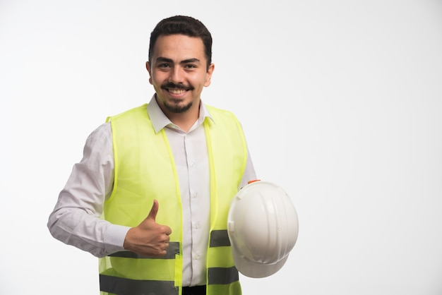 Ingeniero en uniforme sosteniendo un casco blanco.