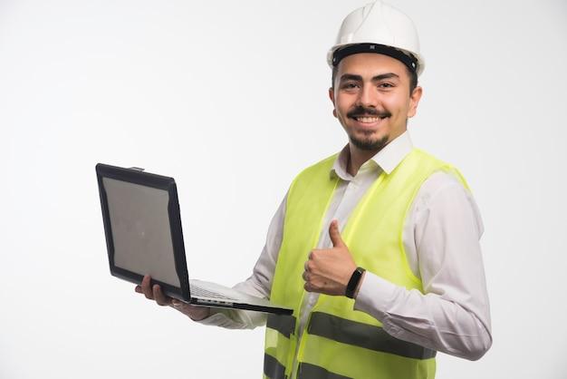 Ingeniero en uniforme sosteniendo una computadora portátil y haciendo pulgar hacia arriba.