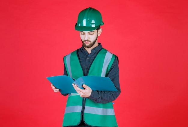Ingeniero en uniforme verde y casco sosteniendo una carpeta azul, abriéndola y leyéndola.