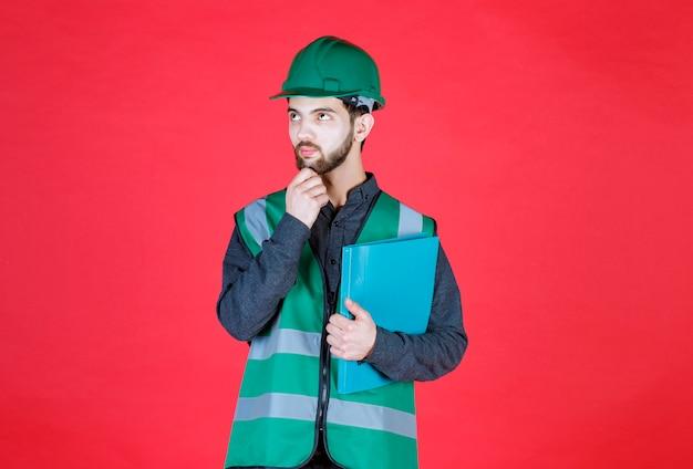 Ingeniero en uniforme verde y casco sosteniendo una carpeta azul y pensando.