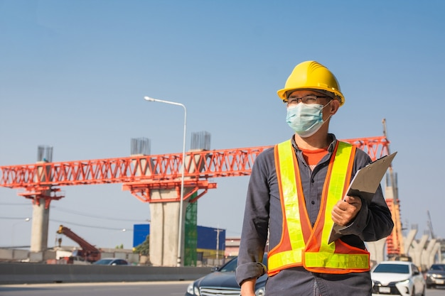 Ingeniero usar mascarilla trabajando en la construcción de carreteras del sitio