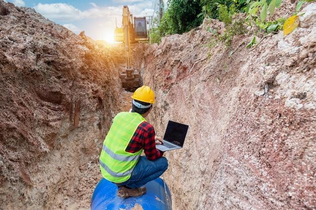 Ingeniero de uso uniforme de seguridad portátil examinando el tubo de drenaje de excavación