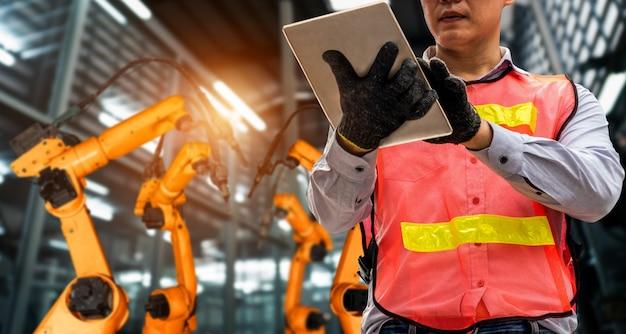 El ingeniero utiliza un software robótico avanzado para controlar el brazo robótico de la industria en la fábrica.