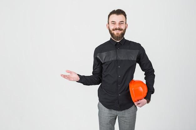 Un ingeniero varón sonriente que sostiene el sombrero duro que se encoge de hombros