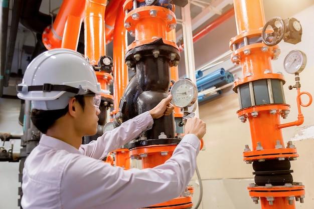 Ingeniero de verificación condensador bomba de agua y manómetro.