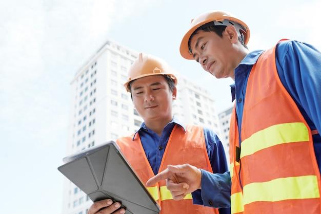 Ingenieros analizando datos en tableta digital