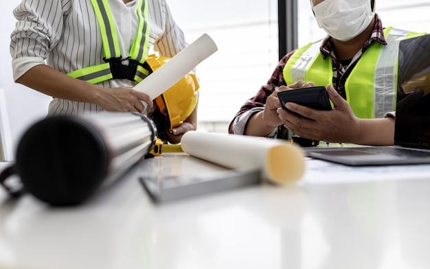 Los ingenieros arquitectos están usando el teléfono en la reunión para discutir los materiales de construcción, se reúnen para planificar la construcción y arreglar algunos diseños. ideas de diseño e interiorismo.