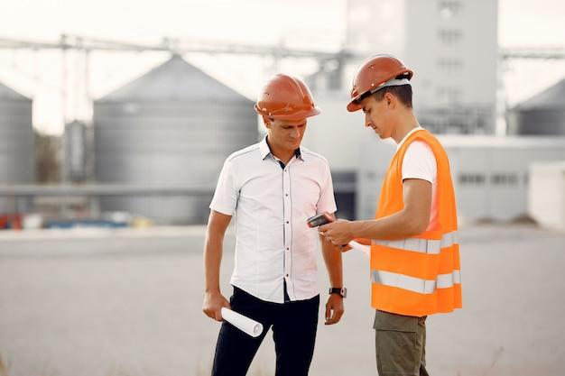 Ingenieros en un casco de pie junto a la fábrica
