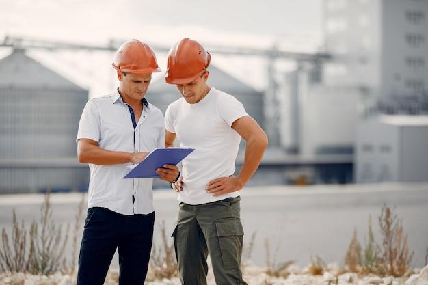 Ingenieros en cascos de pie junto a la fábrica.