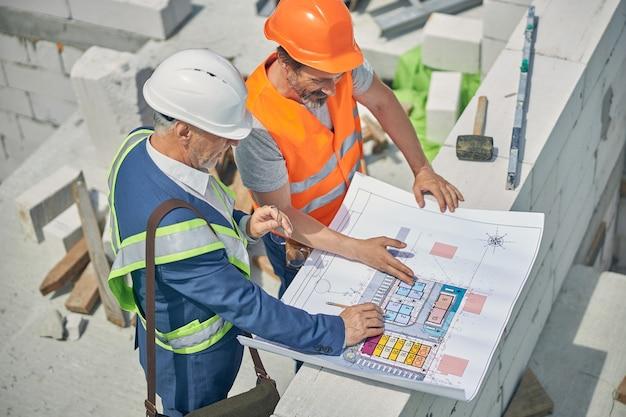 Ingenieros caucásicos en chalecos reflectantes y cascos discutiendo un plan de casa