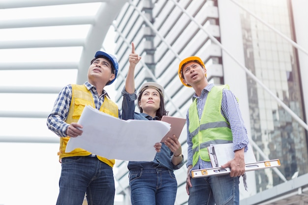 Ingenieros en chaleco de seguridad de pie en obra.