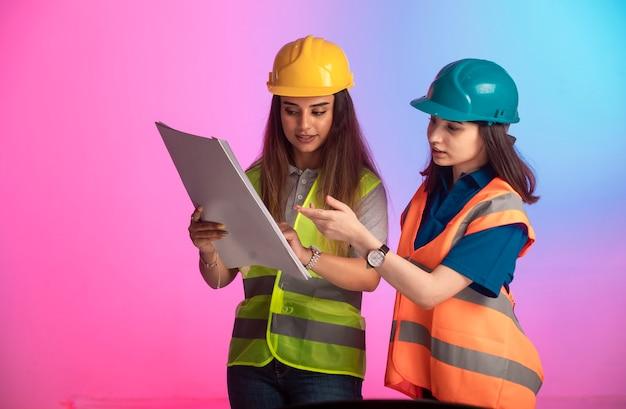 Ingenieros de construcción femeninos trabajando juntos y discutiendo el plan del proyecto en la pared colorida.