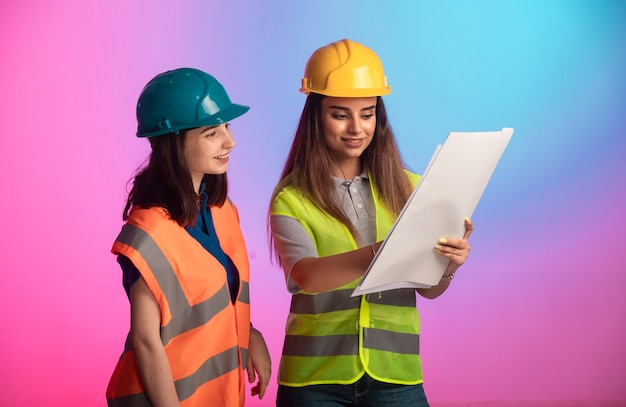 Ingenieros de construcción femeninos trabajando juntos y discutiendo el plan del proyecto