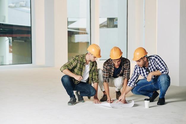 Ingenieros de la construcción jóvenes serios en cascos discutiendo el plan de construcción en el piso en una habitación vacía