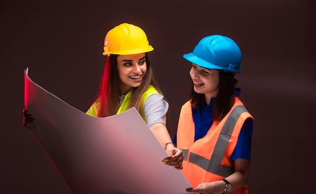 Ingenieros de la construcción mujeres trabajando juntos y discutiendo el plan del proyecto.