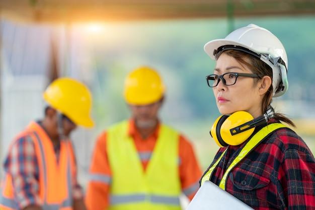 Ingenieros del equipo y arquitecto que trabajan la inspección en el sitio de construcción.