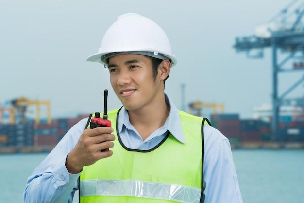 Ingenieros para los hombres del puerto marítimo. usando la radio con el trabajo todo el tiempo.