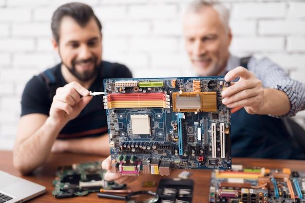 Ingenieros informáticos examinan componente de placa de pc.