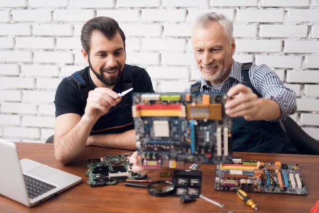 Ingenieros informáticos examinan placa base de pc