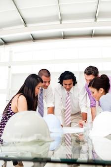 Ingenieros internacionales y su gerente discutiendo planos