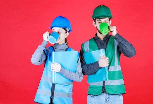 Ingenieros masculinos y femeninos con casco bebiendo de tazas azules y verdes mientras sostienen carpetas de informes.
