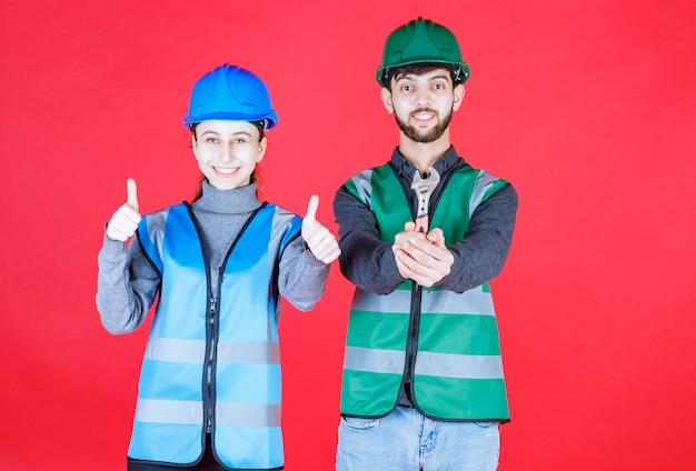 Ingenieros masculinos y femeninos con casco sosteniendo una llave metálica y mostrando un signo de mano positivo.