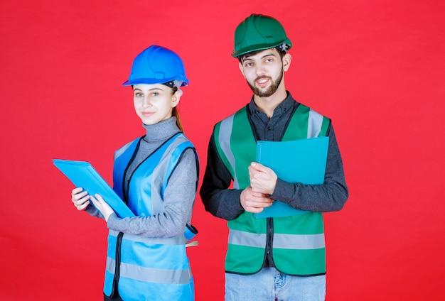 Ingenieros masculinos y femeninos con cascos sosteniendo carpetas azules.