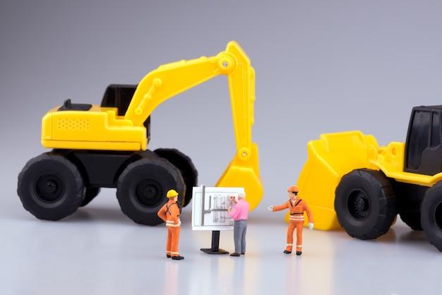 Ingenieros en miniatura y máquinas trabajando en planos de construcción.