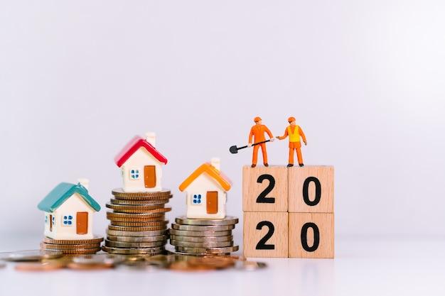 Ingenieros en miniatura de pie con casas en pila de monedas y año 2020 en bloques de madera