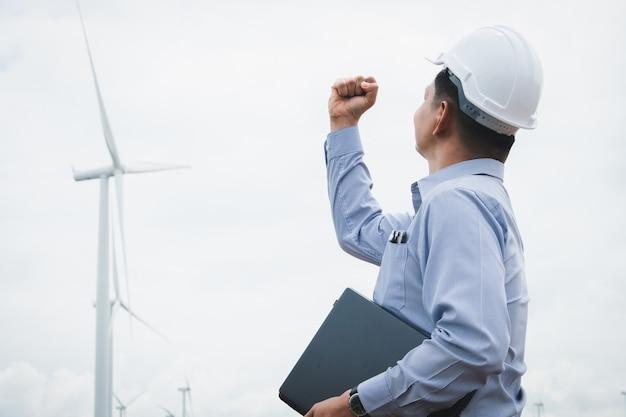 Ingenieros de molinos de viento con máscara facial y trabajando en un portátil con la turbina eólica en segundo plano.